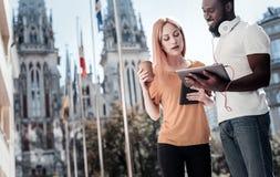 Collègues gais employant le touchpad ensemble tout en se tenant dehors Image libre de droits