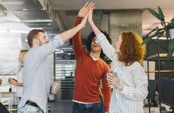 Collègues heureux ayant l'amusement, donnant haut cinq pendant la pause-café images libres de droits