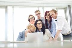 Collègues heureux d'affaires avec l'ordinateur portable discutant dans le bureau créatif Images stock