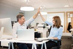 Collègues heureux d'affaires donnant la haute cinq entre eux images stock