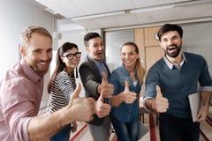 Collègues heureux posant tout droit l'appareil-photo Images libres de droits
