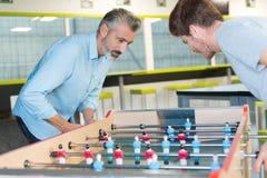 Collègues jouant le jeu de football de table à l'intérieur du bureau images libres de droits