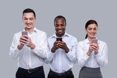 Collègues joyeux dactylographiant à leurs téléphones Image libre de droits