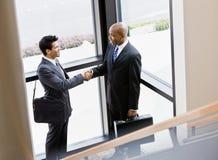 Collègues mâles se serrant la main dans le coin du bureau image libre de droits