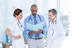 Collègues médicaux concentrés analysant le dossier ensemble Image stock