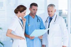 Collègues médicaux concentrés analysant le dossier ensemble Image libre de droits
