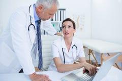 Collègues médicaux concentrés discutant et travaillant avec l'ordinateur portable Photographie stock