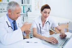Collègues médicaux concentrés discutant et travaillant avec l'ordinateur portable Photo stock