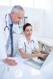 Collègues médicaux concentrés discutant et travaillant avec l'ordinateur portable Photos stock