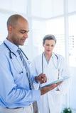 Collègues médicaux concentrés travaillant avec la tablette Image libre de droits