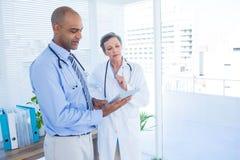 Collègues médicaux concentrés travaillant avec la tablette Image stock