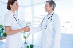 Collègues médicaux de sourire se serrant la main Photos stock