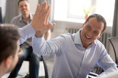 Collègues masculins amicaux heureux donnant le busi haut cinq de célébration photo libre de droits