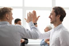 Collègues masculins de sourire donnant la haute cinq dans le bureau célébrant v Images stock