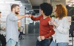 Collègues masculins heureux donnant la bosse de poing pendant la pause-café photo stock