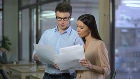 Collègues observant des papiers avec des graphiques et la consultation, prévoyant, gestion du temps banque de vidéos