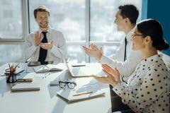 Collègues optimistes battant des mains au cours de la réunion dans le bureau Photographie stock