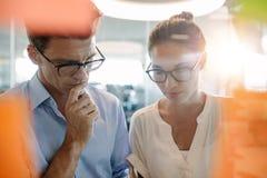 Collègues pensant sur de nouvelles idées d'affaires dans le bureau Images stock