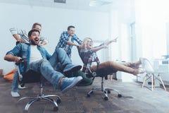 Collègues positifs ayant l'amusement avec des chaises de bureau Photographie stock libre de droits