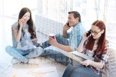 Collègues positifs parlant au téléphone portable Photo stock