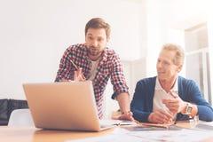 Collègues positifs travaillant ensemble dans le bureau Image stock