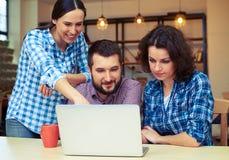Collègues regardant l'ordinateur portable et la discussion Image libre de droits