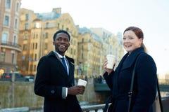 Collègues riants avec du café dans la rue Image stock