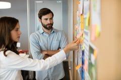 Collègues sérieux d'affaires analysant des diagrammes dans le bureau image libre de droits