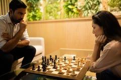 Collègues sérieux d'affaires jouant des échecs photo libre de droits