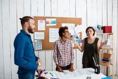 Collègues souriant, parler, discutant des dessins, nouvelles idées à l'arrière-plan de bureau Images libres de droits
