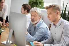 Collègues supérieurs et jeunes focalisés discutant les WI en ligne de projet Image stock