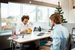 Collègues travaillant dans le bureau le jour de Noël donnant des présents Images stock