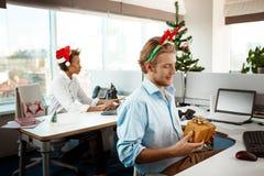 Collègues travaillant dans le bureau le jour de Noël donnant des présents Image libre de droits