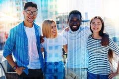 Collègues vigilants souriant et se tenant ensemble Photographie stock