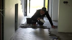 Colla livellata del tuttofare con le mattonelle di forma di esagono di disposizione e della cazzuola sul pavimento stock footage