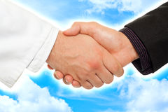 Collaboration 2. Handshake between a businessman and a doctor, with sky background Stock Photo
