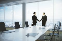 Collaboration concept. Side view of young businessmen shaking hands in contemporary meeting room interior. Collaboration concept. 3D Rendering Royalty Free Stock Image