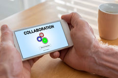 Collaboration concept on a smartphone. Male hands holding a smartphone with collaboration concept Royalty Free Stock Photography