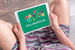 Collaboration concept on a tablet. Woman sitting on the floor with a tablet showing collaboration concept Royalty Free Stock Images