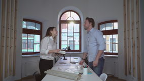 Collaboration in creative agency. Two architect designers working in the office. Creative professional partners celebrating successful idea. Handsome blonde stock footage
