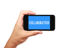 Collaboration. Hand is holding a smartphone with the text Collaboration isolated on white Royalty Free Stock Photography