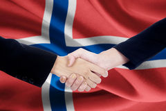 Collaboration handshake with flag of Norway. Picture of a collaboration handshake with two people hands, closing a meeting and shaking hands with flag of Norway Royalty Free Stock Images