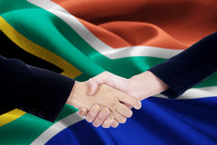Collaboration handshake with flag of South Africa. Image of a collaboration handshake with two worker hands closing an agreement by shaking hands with a national Stock Image