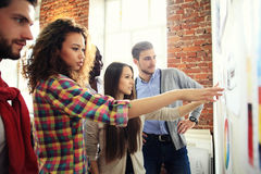 Collaboration is a key to best results. Group of young modern people in smart casual wear planning business strategy. While young women pointing at infographic Royalty Free Stock Photography