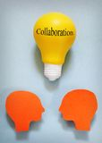 Collaboration teamwork. Two paper heads with  lightbulb - collaboration or team work concept Royalty Free Stock Photos