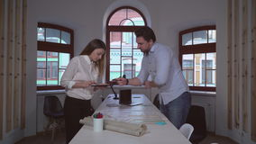 Collaboration two coworkers in design studio. Architect working with assistant. On the desk blueprint building plan. Man pointing woman make notes using digital stock video footage