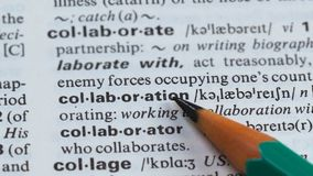 Collaboration word definition pointed in dictionary, mutual project, cooperation stock video footage