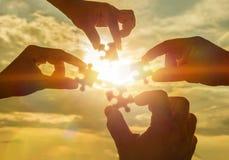 Collaborent quatre mains essayant de relier un morceau de puzzle à un fond de coucher du soleil images stock