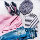 Collage of autumn-winter female clothing set. Pink coat, blue ripped jeans, sriped blouse, knitted hat and black leather boots ove Stock Photo
