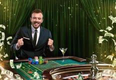 Collage av kasinobilder med rouletten för manlekpoker på tabellen Ung man i dräkten som spelar i kasinot dobbleri royaltyfri bild